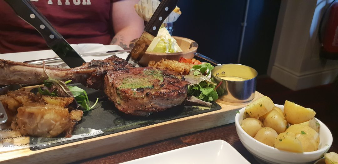 long bone tomahawk sharing steak at miller and carter with side of potatoes